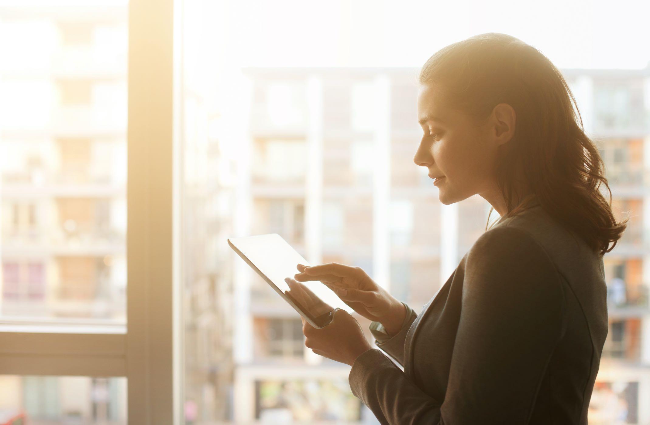 A imagem contém uma mulher em um escritório usando um tablet