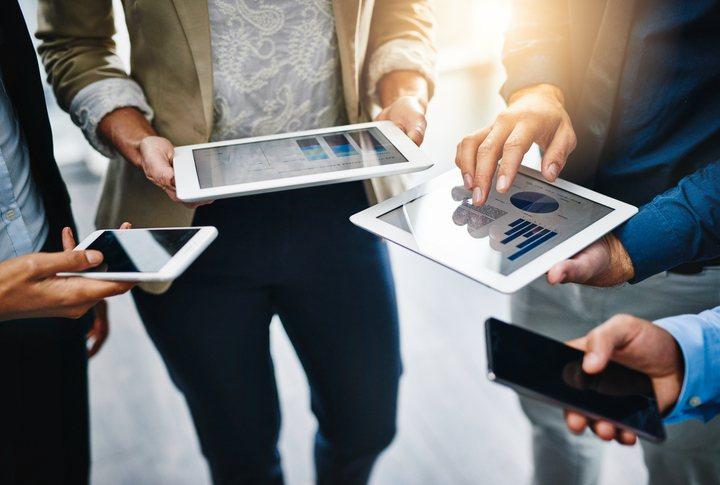 quatro pessoas usando tablets e celulares em uma reunião