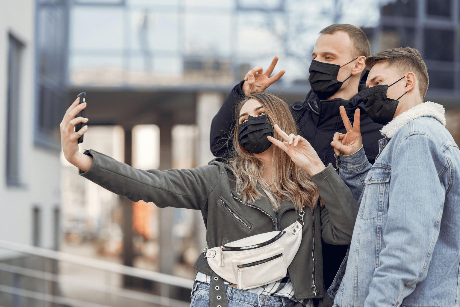três jovens, sendo uma mulher e dois homens, usando mascarás de proteção contra o coronavírus, fazendo sinal de paz e amor com as mãos e olhando para a câmera da mulher para tirar uma foto estilo selfie