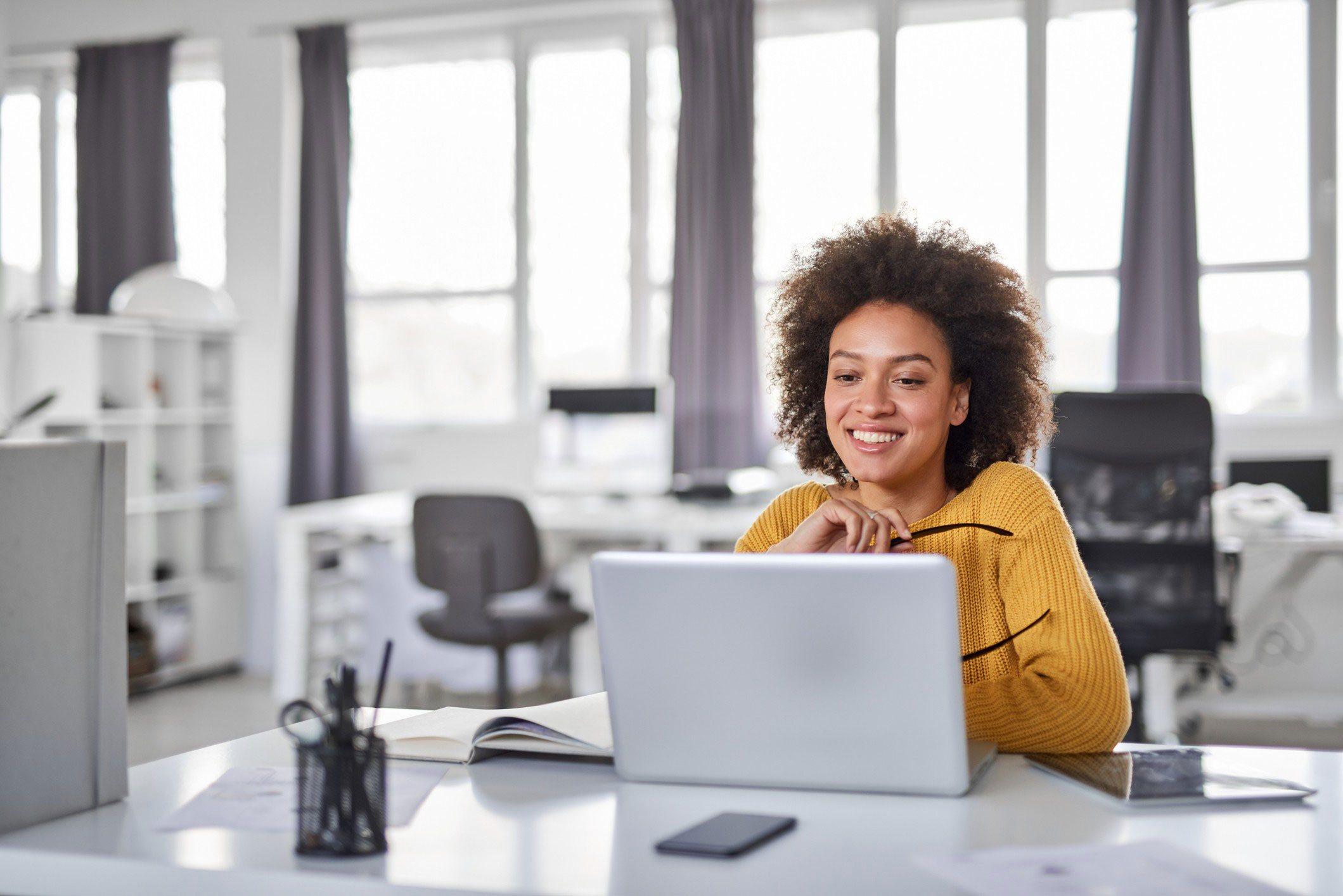 Mulher, parda, com blusa amarela, usando um notebook em um escritório.