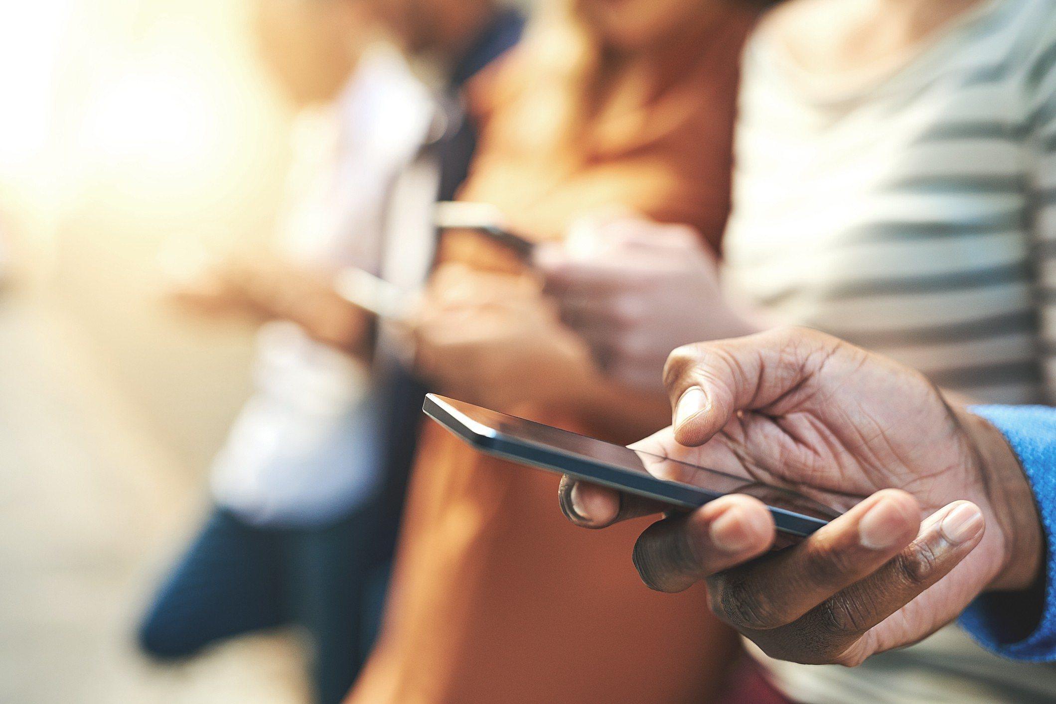 Pessoas com celulares Android e iOS nas mãos